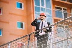 Μηχανικός με το σχέδιο στο χέρι του που μιλά στο τηλέφωνο κυττάρων από την πλευρά κατασκευής Στοκ Εικόνα