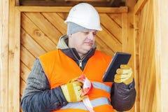 Μηχανικός με το PC ταμπλετών κοντά στο ξύλινο κτήριο Στοκ Εικόνες