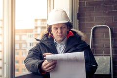 Μηχανικός-οικοδόμος που εργάζεται με τα έγγραφα στο εργοτάξιο οικοδομής Ο εργαζόμενος επιθεωρεί τα σχέδια στο εργοτάξιο οικοδομής Στοκ εικόνα με δικαίωμα ελεύθερης χρήσης