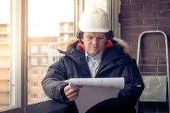 Μηχανικός-οικοδόμος που εργάζεται με τα έγγραφα στο εργοτάξιο οικοδομής Ο εργαζόμενος επιθεωρεί τα σχέδια στο εργοτάξιο οικοδομής Στοκ εικόνες με δικαίωμα ελεύθερης χρήσης