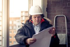Μηχανικός-οικοδόμος που εργάζεται με τα έγγραφα στο εργοτάξιο οικοδομής Ο εργαζόμενος επιθεωρεί τα σχέδια στο εργοτάξιο οικοδομής Στοκ Φωτογραφία