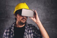 Μηχανικός οικοδόμησης με τα προστατευτικά δίοπτρα VR που διαχειρίζεται το πρόγραμμα κτηρίου στοκ εικόνα