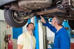 Μηχανικός παρουσιάζοντας πελάτης το πρόβλημα με το αυτοκίνητο Στοκ Φωτογραφία