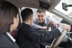 Μηχανικός που δίνει τα κλειδιά αυτοκινήτων στο ζεύγος Στοκ Εικόνα