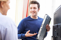 Μηχανικός που δίνει τις συμβουλές για την εγκατάσταση του ψηφιακού εξοπλισμού TV στοκ φωτογραφία