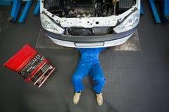 Μηχανικός που βρίσκεται και που εργάζεται κάτω από το αυτοκίνητο στοκ φωτογραφίες
