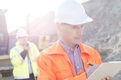 Μηχανικός που γράφει στην περιοχή αποκομμάτων στο εργοτάξιο οικοδομής με το συνάδελφο στο υπόβαθρο Στοκ Φωτογραφίες