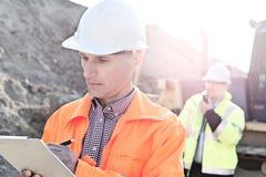 Μηχανικός που γράφει στην περιοχή αποκομμάτων στο εργοτάξιο οικοδομής με το συνάδελφο στο υπόβαθρο Στοκ Εικόνες