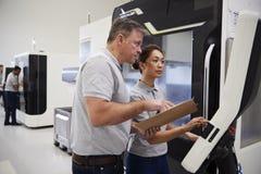 Μηχανικός που εκπαιδεύει το θηλυκό μαθητευόμενο για να χρησιμοποιήσει CNC τη μηχανή στον παράγοντα στοκ εικόνα