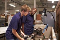 Μηχανικός που εκπαιδεύει τον αρσενικό μαθητευόμενο στη μηχανή άλεσης στοκ φωτογραφία με δικαίωμα ελεύθερης χρήσης