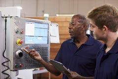 Μηχανικός που εκπαιδεύει τον αρσενικό μαθητευόμενο CNC στη μηχανή στοκ εικόνα με δικαίωμα ελεύθερης χρήσης