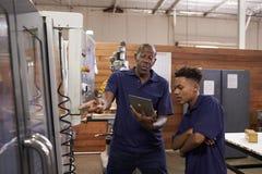 Μηχανικός που εκπαιδεύει το νέο αρσενικό μαθητευόμενο CNC στη μηχανή στοκ φωτογραφίες