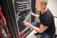 Μηχανικός που ελέγχει τον κεντρικό υπολογιστή υπολογιστών σε Datacenter στοκ εικόνα με δικαίωμα ελεύθερης χρήσης