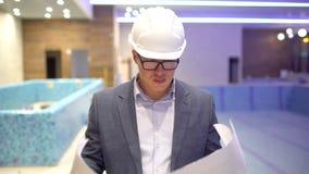 Μηχανικός που εξετάζει την οικοδόμηση των σχεδίων στο εργοτάξιο οικοδομής φιλμ μικρού μήκους