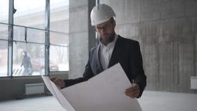 Μηχανικός που εξετάζει την οικοδόμηση των σχεδίων στο εργοτάξιο οικοδομής απόθεμα βίντεο