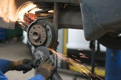 Μηχανικός που επισκευάζει τα φρένα στο κατάστημα επισκευής αυτοκινήτων Στοκ φωτογραφία με δικαίωμα ελεύθερης χρήσης