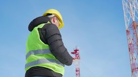 Μηχανικός που εργάζεται στην ψηφιακή ταμπλέτα, με το δορυφορικό δίκτυο τηλεπικοινωνιών πιάτων στον πύργο τηλεπικοινωνιών φιλμ μικρού μήκους