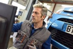 Μηχανικός που εργάζεται στις επιδιορθώσεις αυτοκινήτων στοκ εικόνα