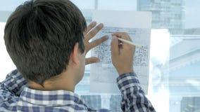 Μηχανικός που εργάζεται στο σχεδιάγραμμα σε ένα σύγχρονο γραφείο απόθεμα βίντεο