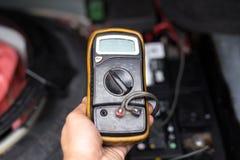Μηχανικός που ελέγχει ένα επίπεδο μπαταριών αυτοκινήτων με το βολτόμετρο Στοκ Φωτογραφίες