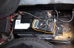 Μηχανικός που ελέγχει ένα επίπεδο μπαταριών αυτοκινήτων με το βολτόμετρο Στοκ φωτογραφίες με δικαίωμα ελεύθερης χρήσης