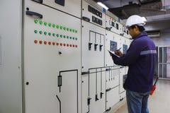 Μηχανικός που ελέγχει το ηλεκτρικό σύστημα στο θάλαμο ελέγχου Στοκ φωτογραφίες με δικαίωμα ελεύθερης χρήσης
