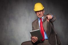 Μηχανικός που θέτει κρατώντας μια ταμπλέτα δείχνοντας το δάχτυλό του Στοκ Εικόνες