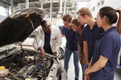 Μηχανικός που καθοδηγεί τους εκπαιδευόμενους γύρω από τη μηχανή ενός αυτοκινήτου στοκ φωτογραφίες