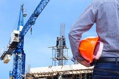 Μηχανικός που κρατά το κίτρινο κράνος ασφάλειας στην οικοδόμηση του εργοτάξιου οικοδομής με το γερανό Στοκ Εικόνες