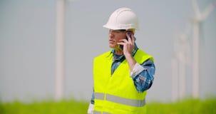 0 μηχανικός που μιλά στο κινητό τηλέφωνο ενάντια στο αγρόκτημα ανεμόμυλων φιλμ μικρού μήκους