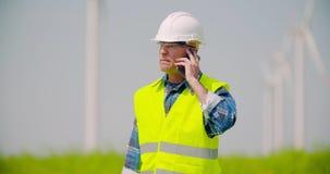 0 μηχανικός που μιλά στο κινητό τηλέφωνο ενάντια στο αγρόκτημα ανεμόμυλων απόθεμα βίντεο