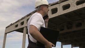 Μηχανικός που μιλά στο έξυπνο τηλέφωνο κοντά στο ατελές κτήριο απόθεμα βίντεο