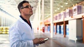 Μηχανικός που μιλά στο τηλέφωνο στη νέα σύγχρονη αποθήκη εμπορευμάτων βιομηχανίας απόθεμα βίντεο