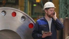 Μηχανικός που μιλά στο smartphone και που χρησιμοποιεί μια ταμπλέτα στο σύγχρονο βαρύ εργοστάσιο βιομηχανίας φιλμ μικρού μήκους