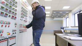 Μηχανικός που μιλά walkie-talkie και τους Τύπους το κουμπί στην επιτροπή μέσα στο θάλαμο ελέγχου απόθεμα βίντεο