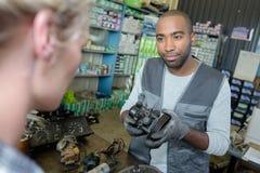Μηχανικός που παρουσιάζει μέρος από δεύτερο χέρι στον πελάτη Στοκ εικόνες με δικαίωμα ελεύθερης χρήσης