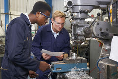 Μηχανικός που παρουσιάζει μαθητευόμενο πώς να χρησιμοποιήσει το τρυπάνι στο εργοστάσιο στοκ εικόνα
