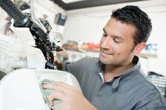 Μηχανικός που σκουπίζει το μπροστινό μηχανικό δίκυκλο με το ύφασμα Στοκ φωτογραφίες με δικαίωμα ελεύθερης χρήσης