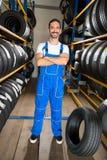 Μηχανικός που στέκεται μεταξύ των ροδών αυτοκινήτων Στοκ Φωτογραφία