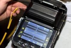 Μηχανικός που συνδέει το καλώδιο οπτικών ινών με Splicer τήξης οπτικής ίνας με το εργαλείο με την επίδειξη στοκ φωτογραφία