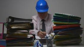 Μηχανικός που φορά τα τεχνικά έγγραφα σημαδιών κρανών στο δωμάτιο αρχείων στοκ εικόνα