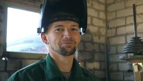 Μηχανικός που χαμογελά και που εξετάζει τη κάμερα Πορτρέτο του ευτυχούς ατόμου με τη γενειάδα που λειτουργεί στο γκαράζ ή το εργα απόθεμα βίντεο