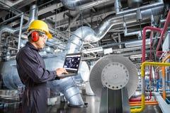 Μηχανικός που χρησιμοποιεί τον υπολογιστή για τη συντήρηση στις εγκαταστάσεις θερμικής παραγωγής ενέργειας στοκ φωτογραφίες με δικαίωμα ελεύθερης χρήσης