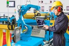 Μηχανικός που χρησιμοποιεί το φορητό προσωπικό υπολογιστή για αυτόματο ρομποτικό ελέγχου Στοκ Εικόνες