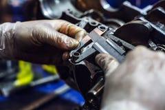 Μηχανικός προσεκτικά μετρά το επιθυμητό στοιχείο Στοκ εικόνες με δικαίωμα ελεύθερης χρήσης