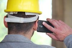 Μηχανικός σε ένα εργοτάξιο οικοδομής που κάνει μια επιχείρηση να καλέσει Στοκ Φωτογραφία