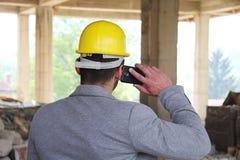 Μηχανικός σε ένα εργοτάξιο οικοδομής που κάνει μια επιχείρηση να καλέσει Στοκ Εικόνα