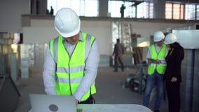Μηχανικός στα σκληρά καπέλα που έχουν τη συνομιλία, φορητός προσωπικός υπολογιστής, κτήριο εσωτερικών κάτω από την οικοδόμηση 4 Κ απόθεμα βίντεο