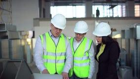 Μηχανικός στα σκληρά καπέλα που έχουν τη συνομιλία, φορητός προσωπικός υπολογιστής, κτήριο εσωτερικών κάτω από την οικοδόμηση αερ φιλμ μικρού μήκους