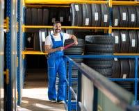 Μηχανικός στην μπλε ομοιόμορφη στάση στο ελαστικό αυτοκινήτου αποθεμάτων Στοκ Εικόνες